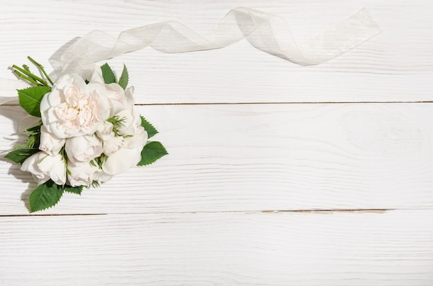 Bunch of white roses on white table. top view