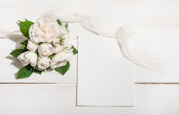 Bunch of white roses on white table with empty card. top view