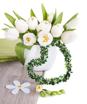 Bunch of white tulips and matching spring decorations on wood isolated on white