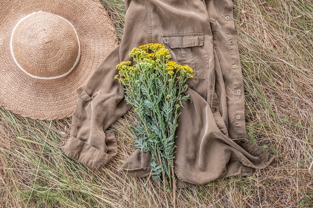 A bunch of wild field flowers on faded grass and country hat. rural still life flat lay: bouquet lies on a shirt  in the grasses or hay.
