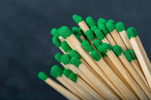 A bunch of wooden matches with green gray