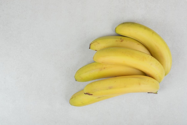 Bunch of yellow bananas on gray surface.