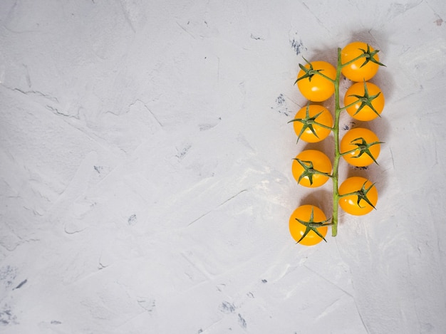 Bunch of yellow cherry tomatoes on white background