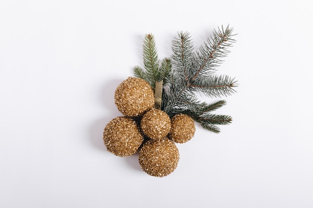 Bunch of yellow christmas balls and fir branches on a white background