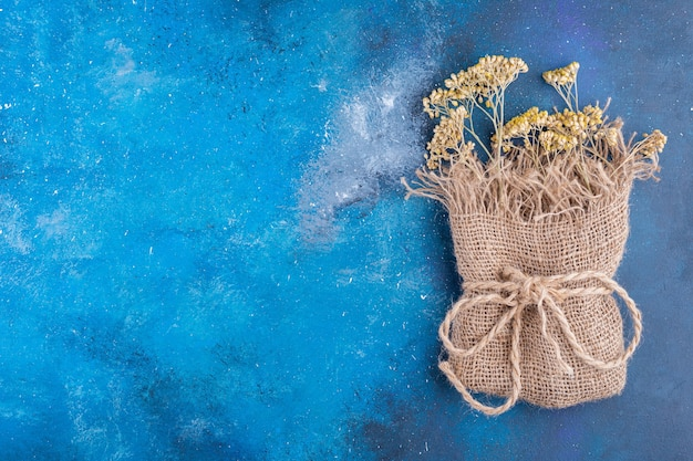 Bunch of yellow dried flowers in sackcloth on blue surface.