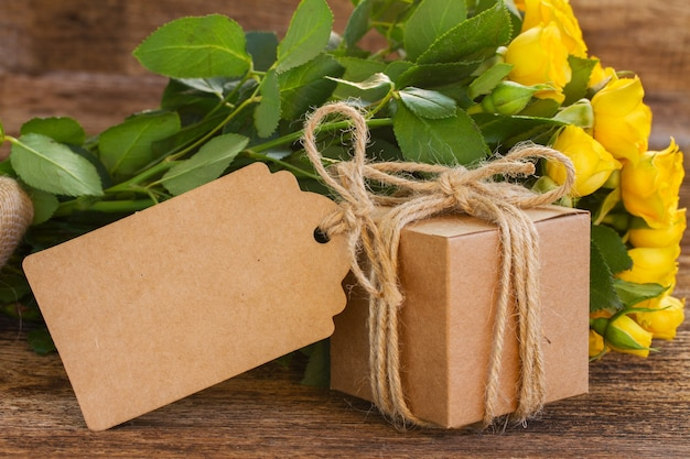 Bunch of yellow roses on wooden with empty paper tag gift box close up
