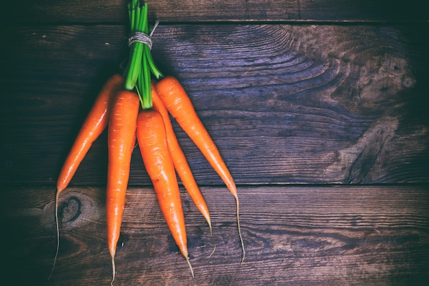 Bunched fresh carrots on a wooden table