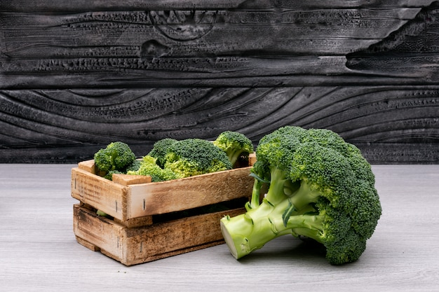 Bunches of broccoli in wooden box near the whole fresh broccoli
