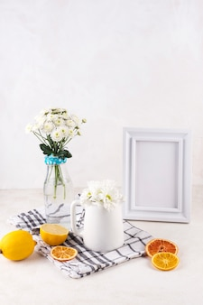 Bunches of fresh flowers in vase near fruits and photo frame