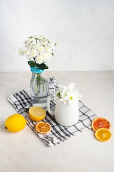 Bunches of fresh flowers in vase and pitcher near fruits