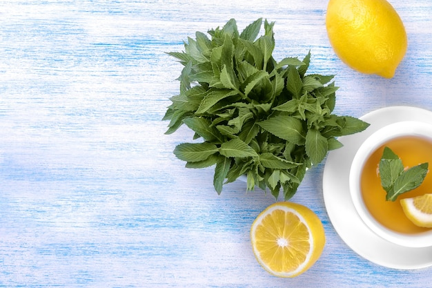 Bunches of fresh mint with lemon and a cup of tea on a blue wooden background