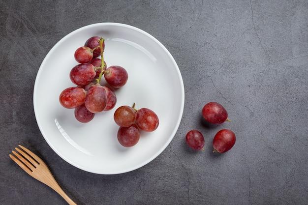 Grappoli di uva rossa matura fresca sulla superficie scura.