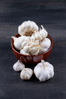 Bunches of garlic in bowl on dark wooden table
