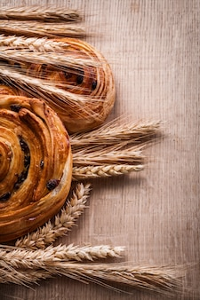 Bunches of golden wheat ears pastry with raisins on oaken wooden board