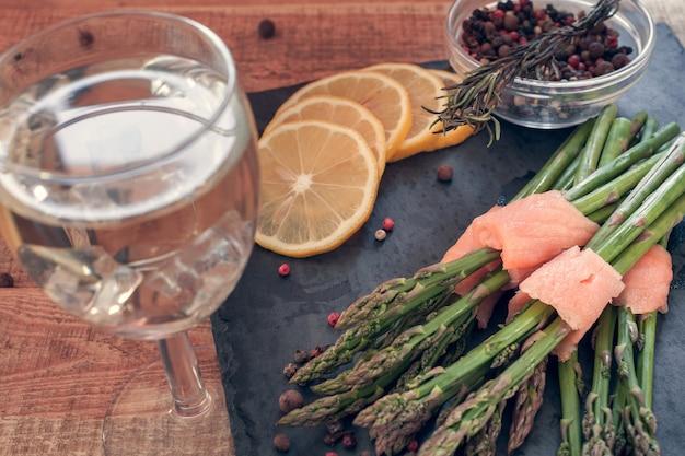 Пучки спаржи, завернутые в лосось со специями и вином на черной доске