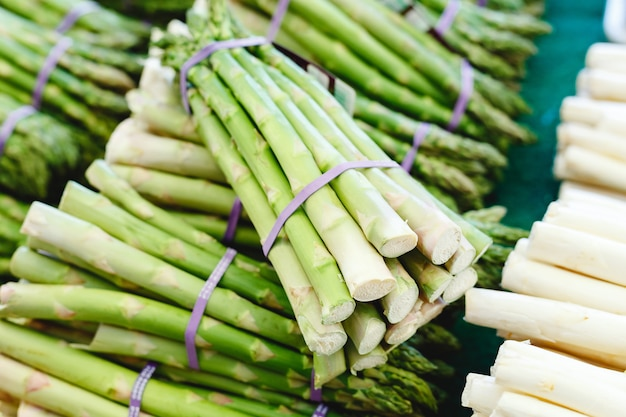 ファーマーズマーケットでの販売のための新鮮な生のグリーンオーガニックアスパラガス野菜の束。ビーガンフードのコンセプトです。ストックフォトグリーンアスパラガスをクローズアップ。