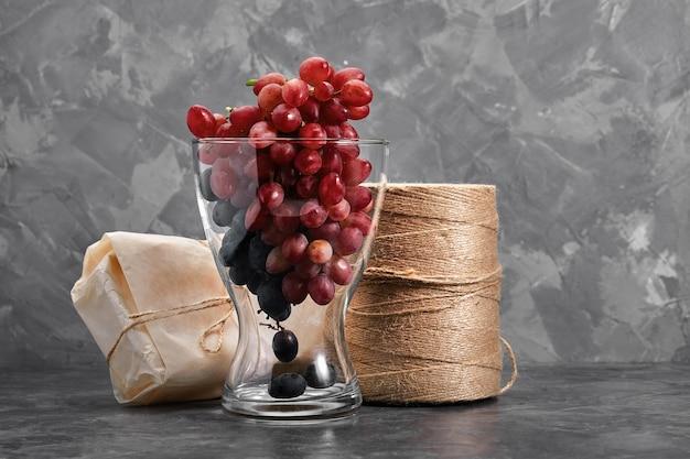 콘크리트 조직 표면에 신선한 익은 어두운 포도의 큼. 레드 와인 포도. 음식의 정물. 자연. 가을 수확. 채식 영양. 포도주 양조장.
