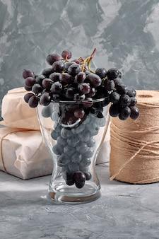 Грозди свежего спелого красного винограда на бетонной текстурной поверхности. филиал розового винограда. красное вино виноград. темный виноград. натюрморт из еды. природа. осенний урожай. вегетарианское питание. винодельня.