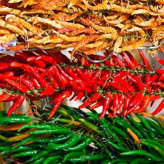 ファーマーズマーケットの赤と緑の温かい肌寒い唐辛子の束