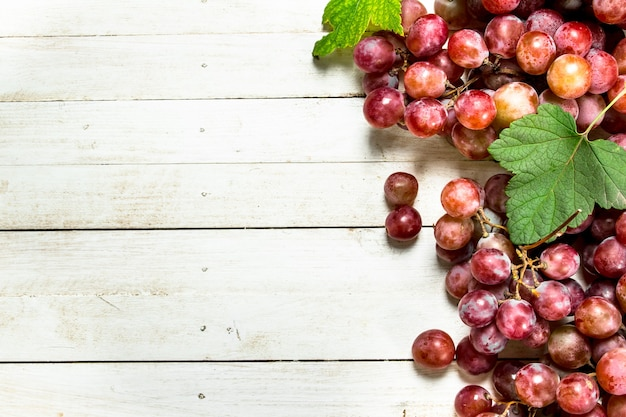 白い木製のテーブルの上に葉を持つ赤ブドウの束。