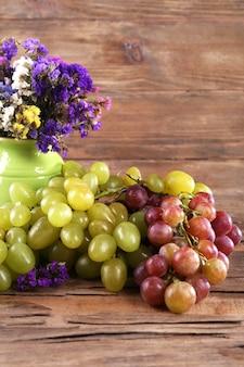 잘 익은 포도의 큼과 나무 테이블에 나무 테이블에 신선한 꽃의 꽃병