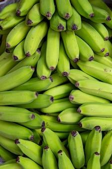屋外の露店で熟していないバナナの束