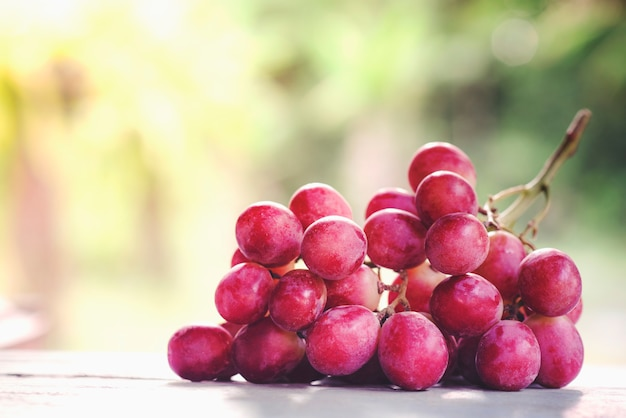 Bunches of ripe red grape on wooden wooden texture, natural green background