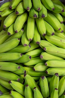 Bunches of unripe banana at an outdoor market stall