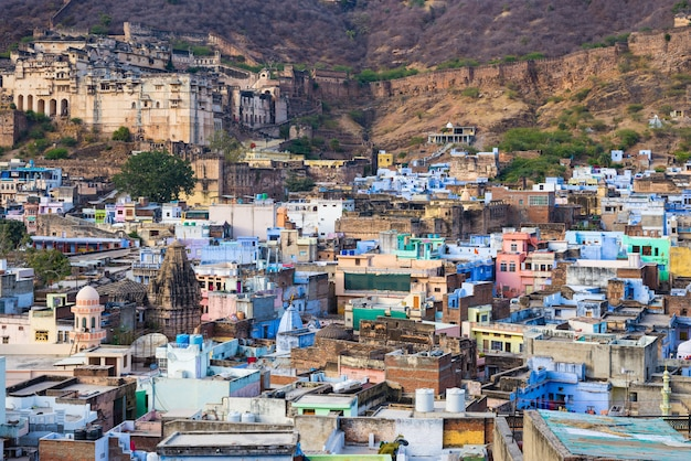 Bundi cityscape, travel destination in rajasthan, india. the majestic fort perched on mountain slope overlooking the blue city.  wide angle view.