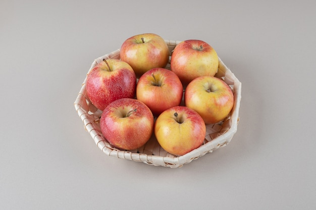 A bundle of apples in a basket on marble
