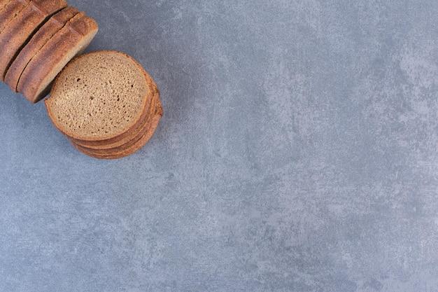 Fascio di fette di pane nero su fondo marmo. foto di alta qualità