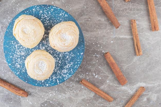 Fascio di bastoncini di cannella intorno ai biscotti a scaglie su una tavola su una superficie di marmo