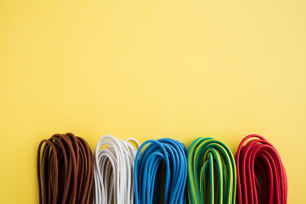 Bundle of colorful electronic wire over plain yellow backdrop