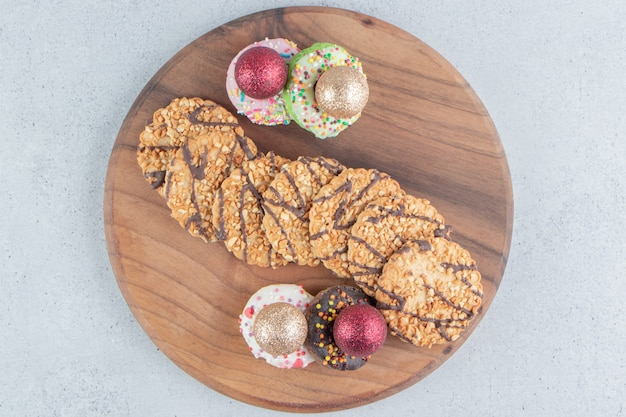 Bundle of cookies and bauble-topped donuts on a board on marble background.