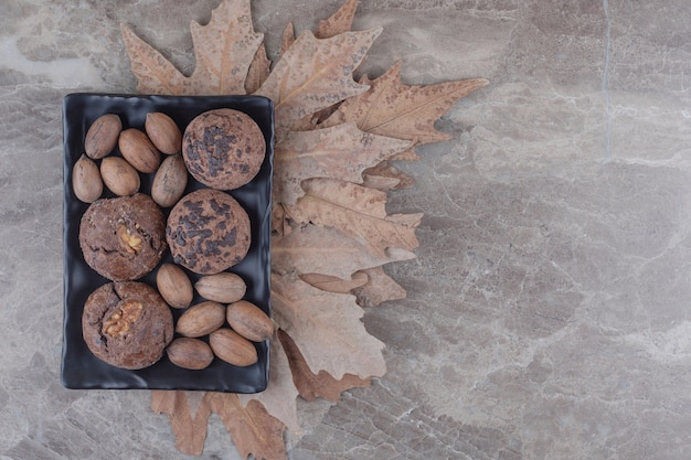 A bundle of cookies and pecan nuts on a platter and a bunch of plane tree leaves on marble