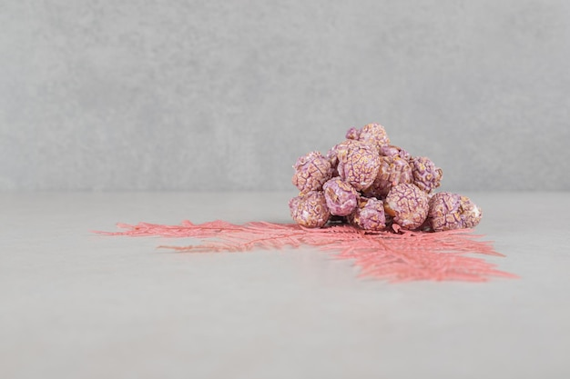 Bundle of decorative leaves adorning a small heap of popcorn candy on marble table.