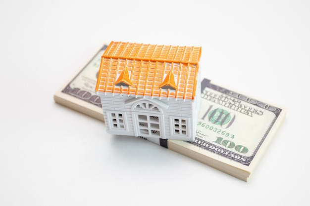 Bundle of dollars bills and house model.