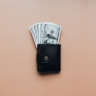 Bundle of dollars in purse on beige background. high quality photo