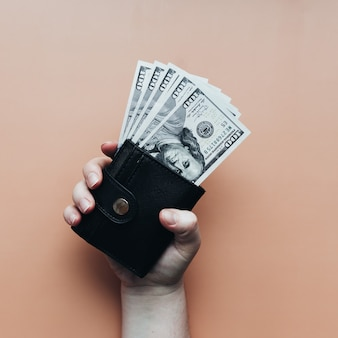 Bundle of dollars in purse and hand on beige background. high quality photo
