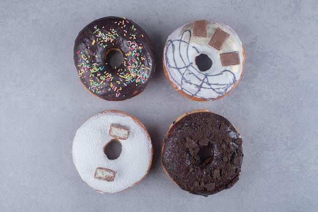 Сложите пончики с различными начинками на мраморной поверхности.