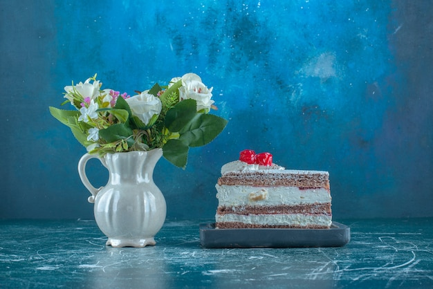Bundle of flowers next to a small slice of cake on blue background. high quality photo