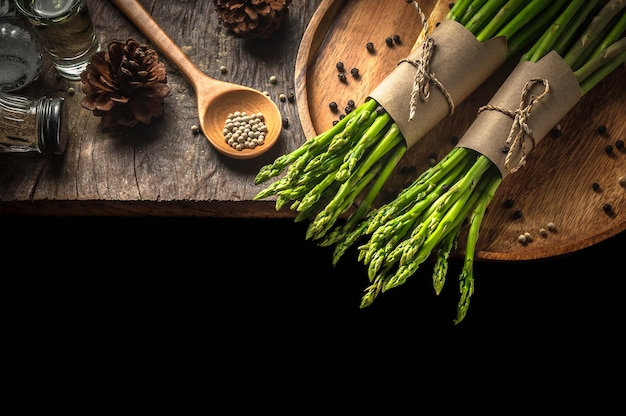Bundle of fresh green asparagus on a rustic wooden table with copy space.