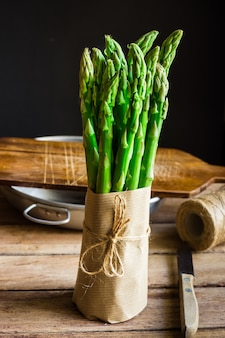 Bundle of fresh green asparagus wrapped in craft paper tied with twine standing on wood kitchen table