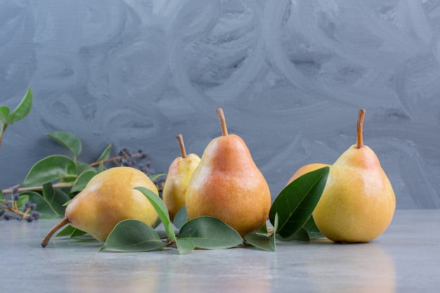 Bundle of leaves and pears on marble background.