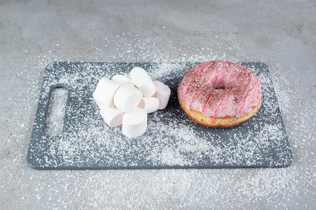 Bundle of marshmallows and a donut on a coconut power covered board on marble surface