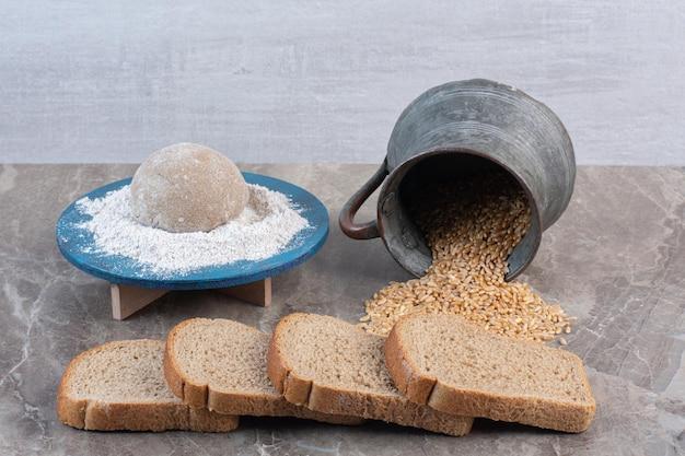 빵 조각, 밀가루 플래터 및 대리석 배경에 쏟은 밀의 번들. 고품질 사진