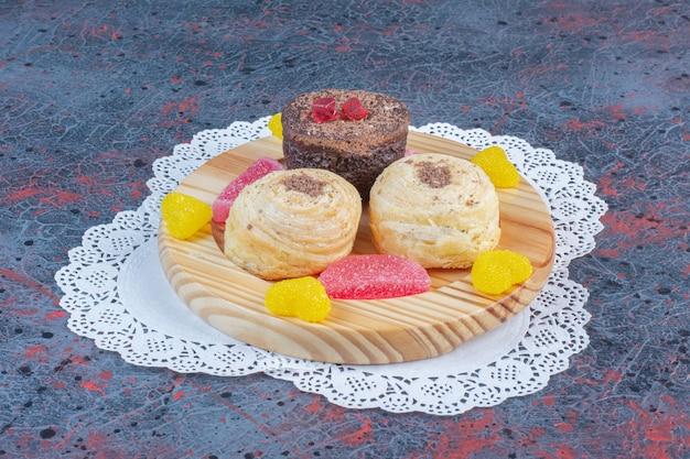 抽象的なテーブルの上の木製の大皿にケーキとマーマレードの束。