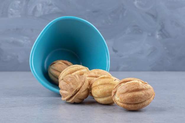 카라멜로 채워진 쿠키 볼 번들이 대리석의 작은 그릇에서 쏟아졌습니다.