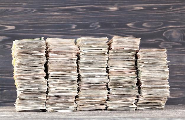 Пачка наличных старых счетов, лежащих на столе, крупным планом