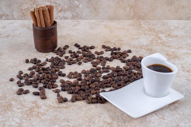 흩어져있는 커피 원두와 커피 한잔 옆에 나무 컵에 계피 스틱 번들